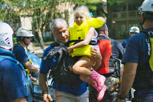 little girl being carried by rescue worker