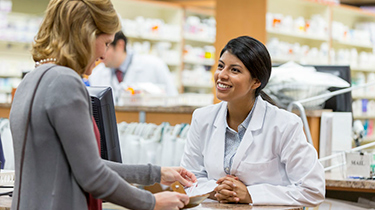 Woman at a speaking to a pharmacist at a pharmacy