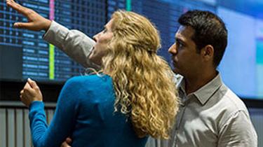 Man and woman looking at data on big screen