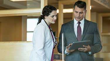 Female doctor looking at male business man's computer tablet