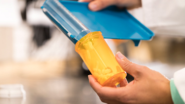 Hands holding a prescription pill counter dropping pills into an orange bottle