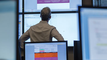 Man examining computer screens