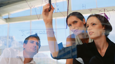 Woman writing on white board as two co-workers watch
