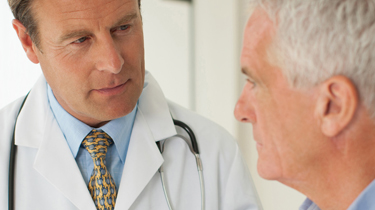 A male doctor listening to his male senior patient.