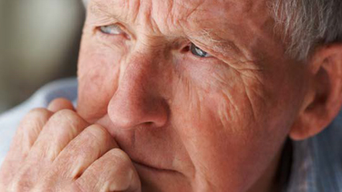 Male senior resting his chin on his fist looking off into the distance thinking
