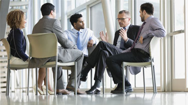 Image of business professionals sitting together in a circle