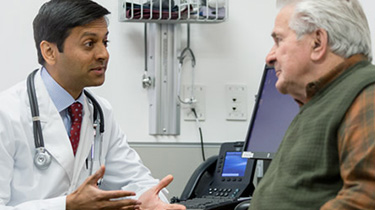 Doctor in clinic talking to his senior male patient