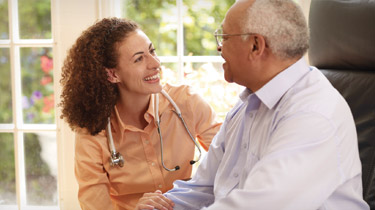 Health care worker visiting a male senior patient at home