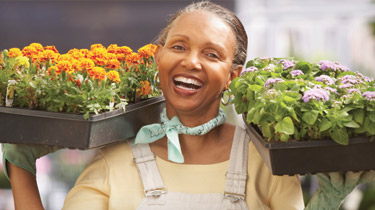 Woman holding flower plant seedlings on her shoulders