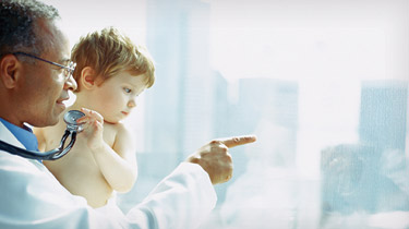 Doctor holding a baby near a window while the baby plays with his stethoscope