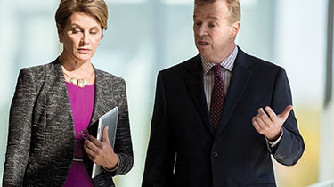 Business man speaking to business woman holding tablet while walking