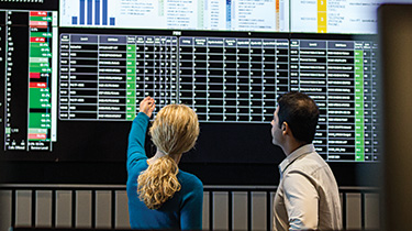 A man and woman reading data on a large computer screen on the wall
