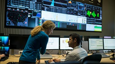 Two people working in front of multiple large screens showing data