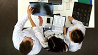 An overhead view of three people working in a healthcare environment.