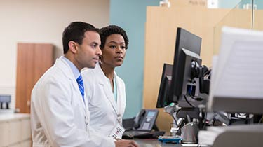 Two medical professionals looking at a computer monitor together
