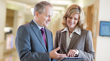 Man and woman in business suits looking at a computer tablet