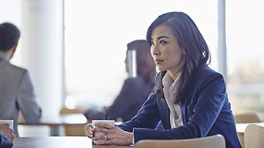 Woman dressed in business attire looking upward