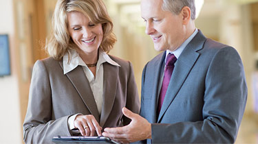 Two business professionals looking at information on a mobile device