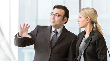 Man and woman, both in business attire, engaged in conversation.