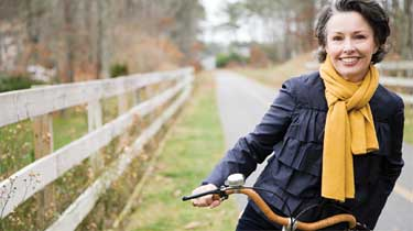 Mature woman stopped on her bike along a fence and smiling